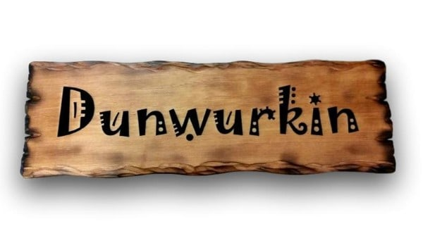 wooden sign burnt with flame close up photo of an outdoor rustic cedar sign for a retirement gift reads-dunwurkin