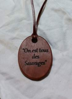 """handmade pendant necklace crafted from jarrah with fine kangaroo leather strap engraved with text """"On est tous des Sauvages"""""""