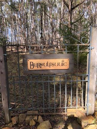 victorian ash sign hanging on gate reads bernulfsuuic (restaurant logo)