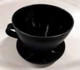 Svart kopp med litet fat
