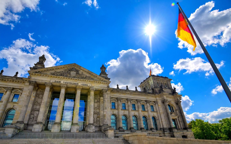 Riksdagsbygningen i Berlin med det tyske flagget. Foto