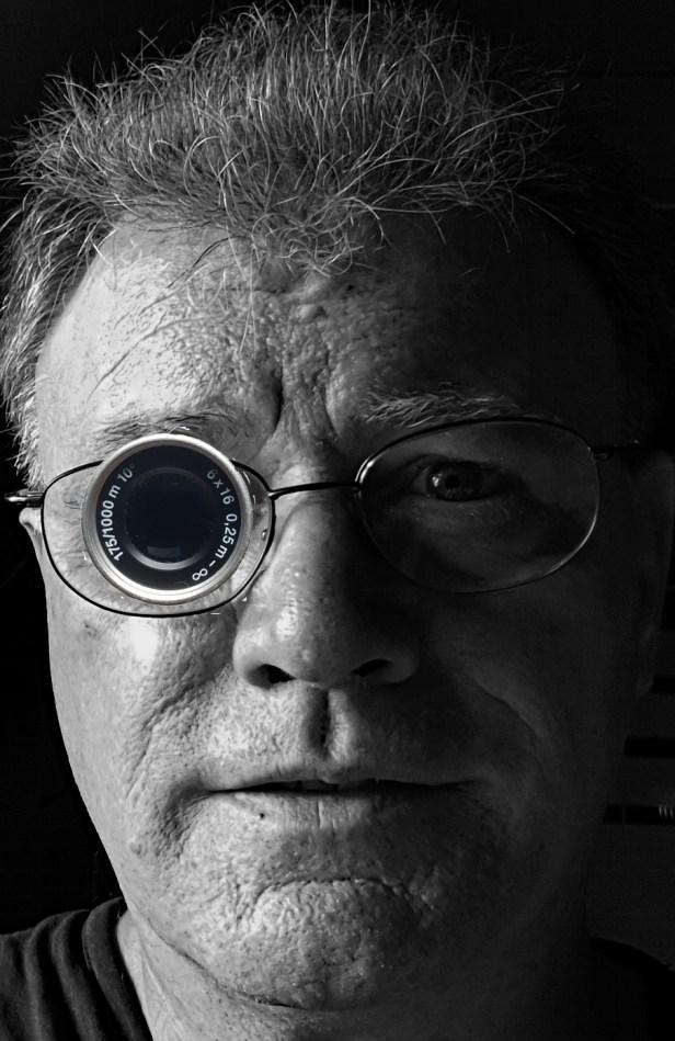Visage de Thierry VAN DEN BIL en gros plan avec une loupe monoculaire montée sur lunettes devant l'oeil droit- Photo en noir et blanc