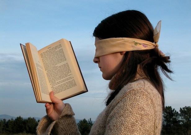 photo présentant une jeune fille de profil gauche, les yeux bandés, un livre ouvert que sa main droite place devant le visage, sur fond de ciel bleu. Ses cheveux sont châtains foncés. Elle porte un pull en laine beige à col roulé.