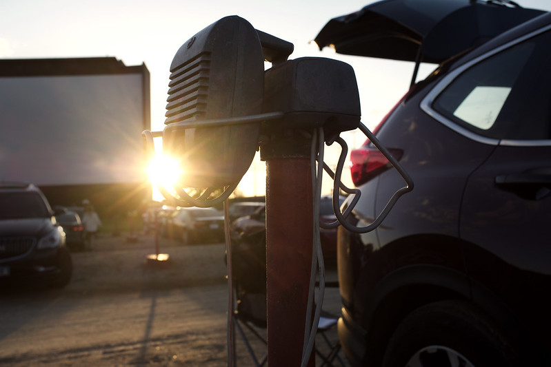 sun setting behind the screen of a drive-in movie theater highlighting the mobile radio and back of car