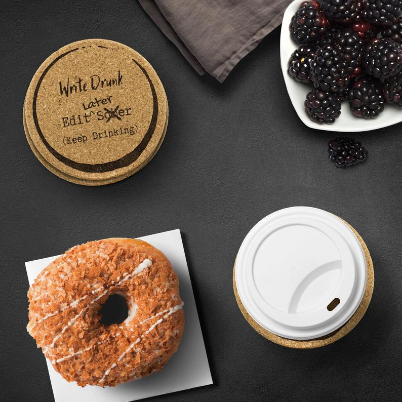 coasters from procrastiplanner that say write drunk, edit later with a cup of coffee, a donut and blackberries on a dark background