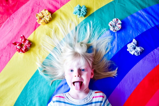 emotional outbursts girl on rainbow bed with air scrunchies