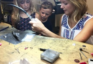 Dallas, Texas artist Hannah Brown in jeweler's studio working at her bench