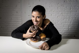 young attractive latin woman sitting at table eating dish full of junk sugary unhealthy food such as chocolate donut and muffin cake in sugar addiction and hell with diet concept