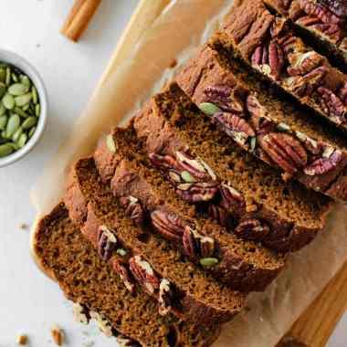 Vegan sweet potato bread sliced on a wooden serving board.