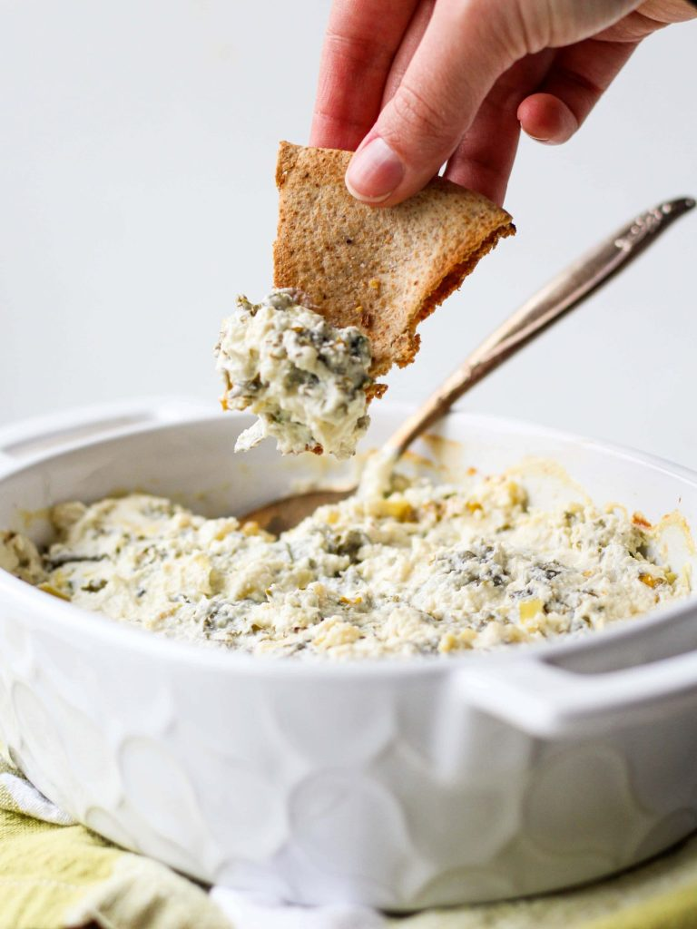 This easy Healthy Kale & Artichoke Dip recipe is a healthier take on traditional spinach & artichoke dip, lightened up with greek yogurt. I used kale instead of spinach to change things up and the result is delicious and nutritious! Serve it up at your next holiday party or family gathering.