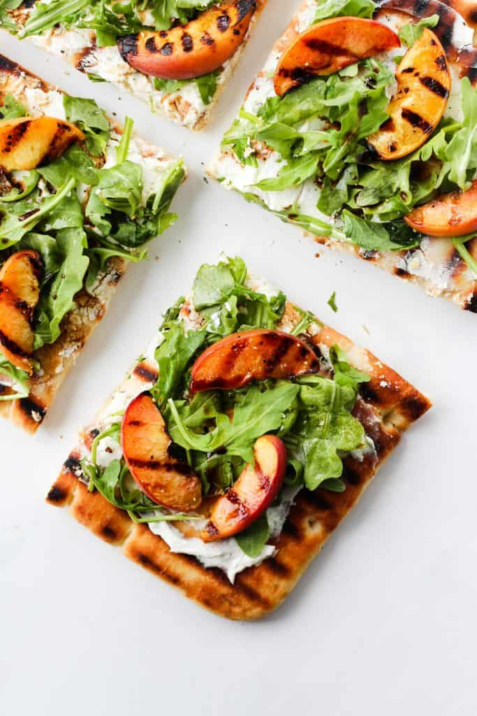 Soft, lightly-grilled flatbread with caramelized grilled peaches, creamy goat cheese, arugula and balsamic drizzle. This grilled peach and arugula flatbread pizza with goat cheese and balsamic is an easy and delicious summer meal. Ready in 30 minutes or less!