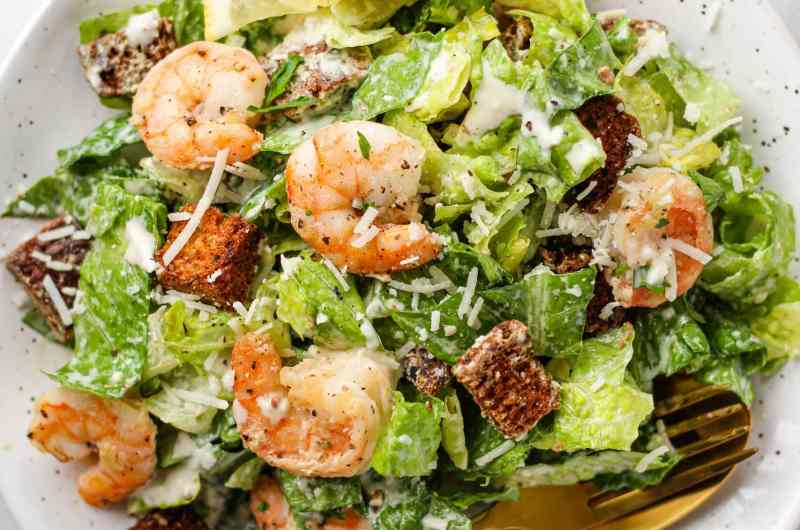 Make a restaurant-style Caesar Salad at home! This Healthy Caesar Salad recipe is made with crisp romaine, homemade croutons, a homemade creamy caesar dressing and optional lemon garlic shrimp.