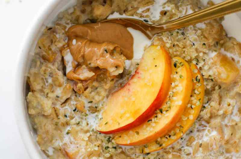 Easy stovetop Peaches and Cream Oatmeal made with rolled oats, fresh peaches, hemp seeds, milk, vanilla, honey, and a splash of half & half.