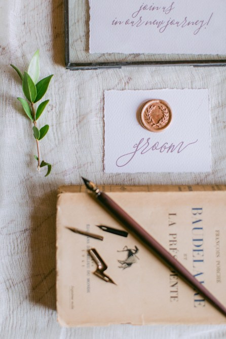 Beautiful intricate wedding invitation calligraphy styled by professional photographer and designer for bride and groom and photographed on vintage textures and fabrics.