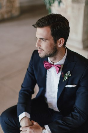 Groom in his wedding suit by Uomo Sartoriale Athens posing for elegant portraits sitting in an armchair facing the window.