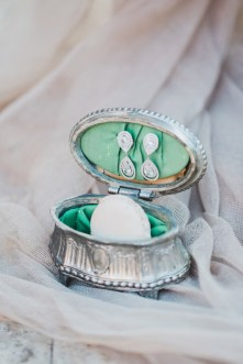 Inspirational detail shot of bridal jewellery styled and photographed in a vintage box on the wedding day session in Athens.