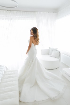 Professional wedding day portrait, beautiful smiling bride posing for the wedding photographer in her luxury bridal villa suite in Crete against white windows.