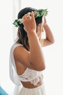 Beautiful boho bride putting on handmade green flower wreath and checking her reflection in the mirror during bridal preparations for a beach ceremony.
