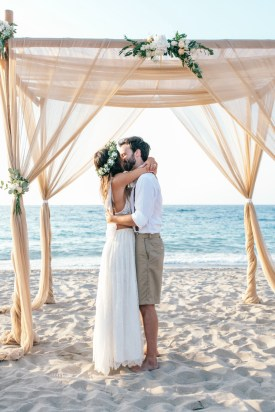 Bride and groom kissing for the first time and husband and wife under the wedding canopy set up and decorated on the beach for a symbolic wedding ceremony.