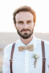 Wedding photograph of the groom posing for portraits for professional photographer standing on the beach with stunning sunset in the background.