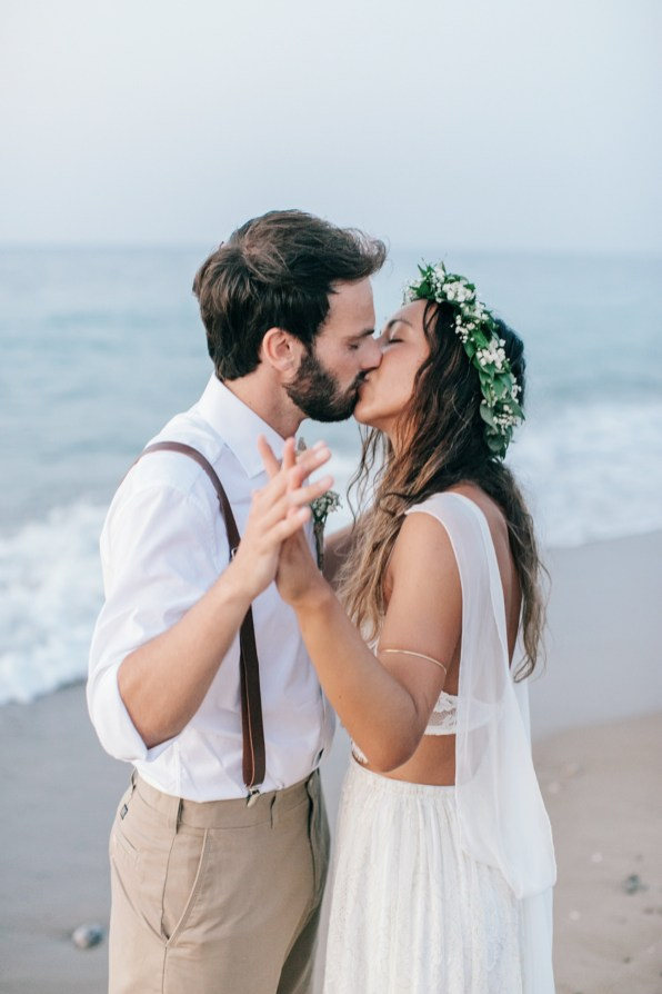 Professional image of bride and groom kissing gently on the sea shore on a sandy beach in Crete after their beach wedding ceremony.
