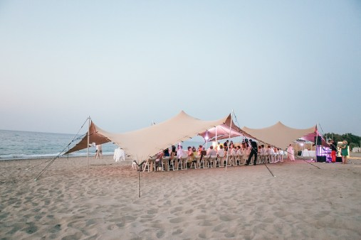 Wedding reception set up under a beduin tent on a beach of Rethymno at sunset.