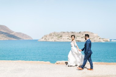 Professional wedding photosession in Elounda Crete, bride and groom walking and posing with Spinalonga island and sea view in the background.