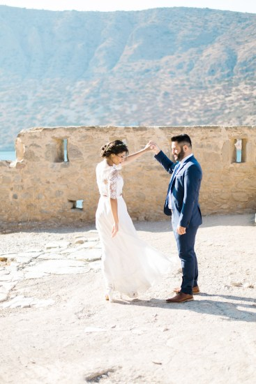 Professional wedding portrait photosession in Crete, bride and groom posing while taking a walk along Spinalonga island, it's historical ruins, church and sites, sea and majestic olive trees in the background.