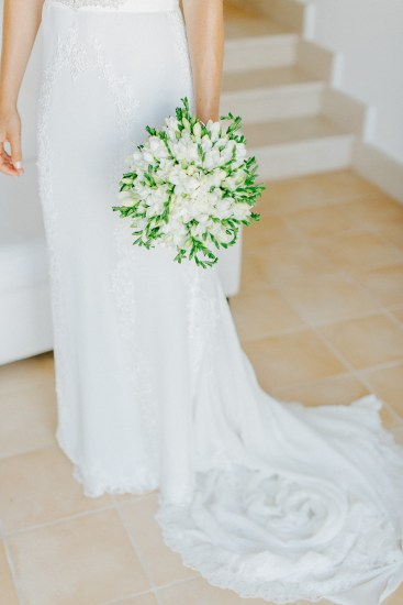BProfessional image of a bridal bouquet being held by the bride with the background of white Pronovias dress.