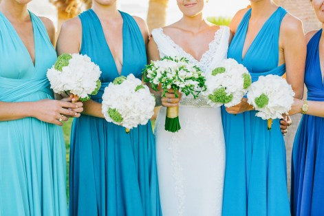 Professional image of a bridal and bridesmaids' bouquets being held by the bride and her friends with the background of white Pronovias dress and blue mismatched dresses by Two Birds bridal boutique.