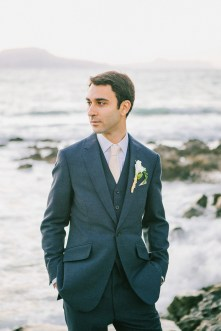 Professional portrait of groom posing for the wedding photographer wearing tailored suit and flower boutonniere captured after the wedding ceremony in palm tree wedding estate in Rethymno Crete with a sunset sea view background.