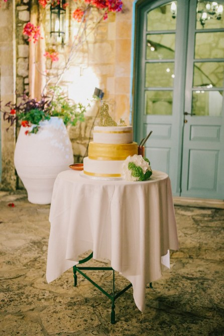 Artisan wedding cake professionally photographed against the background of stony walls and blue Greek windows of Grecotel Agreco farm.