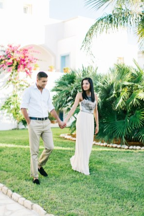 Engaged couple walking along the green lawn of their luxury resort in Crete during their pre wedding engagement photosession.