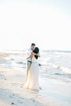 Engaged couple kissing on the beach in Crete during their pre wedding engagement photosession at sunset.