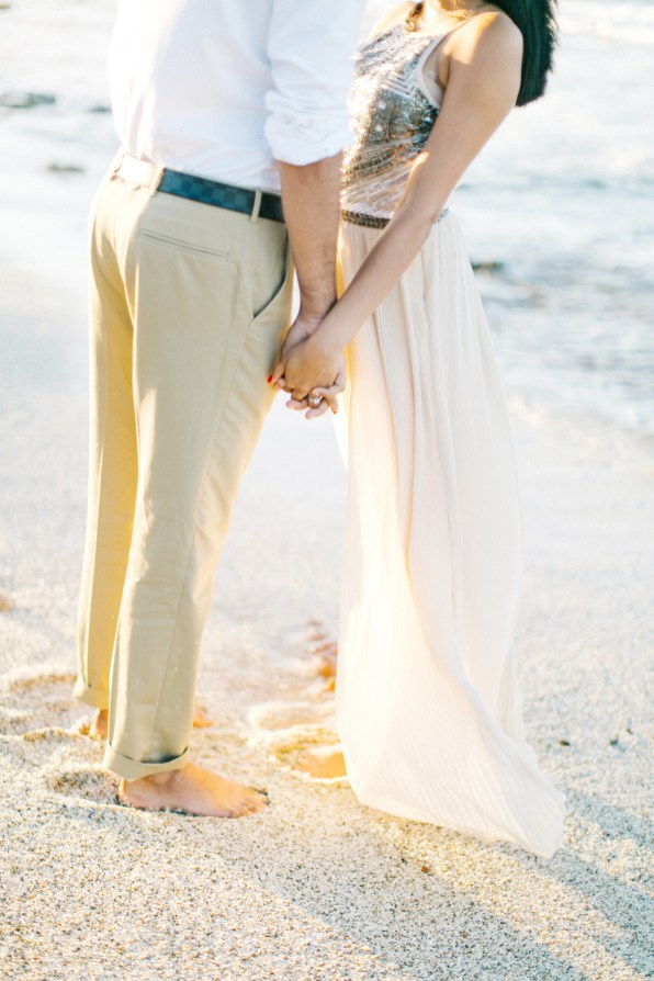 Close up image of young couple holding hands when posing on the beach in Crete during their pre wedding engagement photosession at sunset.