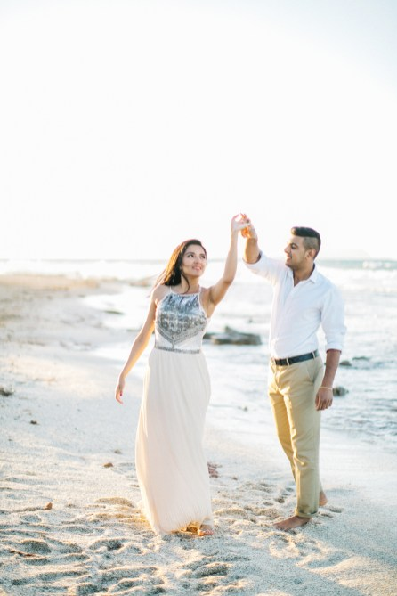 Beautiful engaged couple dancing on the beach in Crete during their pre wedding engagement photosession at sunset.