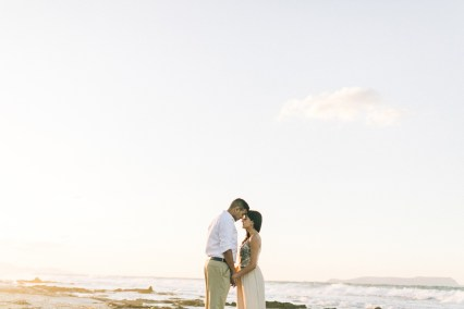 Landscape portrait of young couple holding hands when posing on the beach in Crete during their pre wedding engagement photosession at sunset.