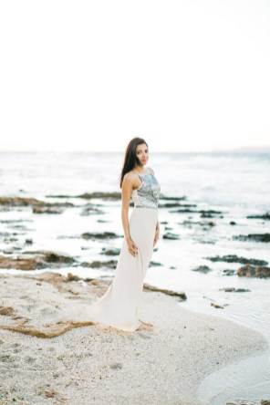Engaged woman posing for portraits on a stunning sandy beach in Crete during professional pre wedding engagement photoshoot.