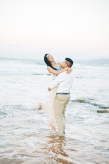 Engaged couple posing for portraits, having fun and laughing on a stunning sandy beach in Crete during professional pre wedding engagement photoshoot.
