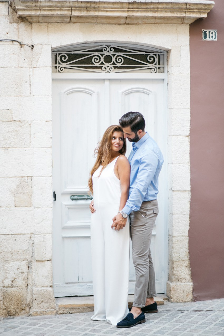 beautiful couple posing for professional photographer in the old town of Chania Crete with rich background of Greek architecture.