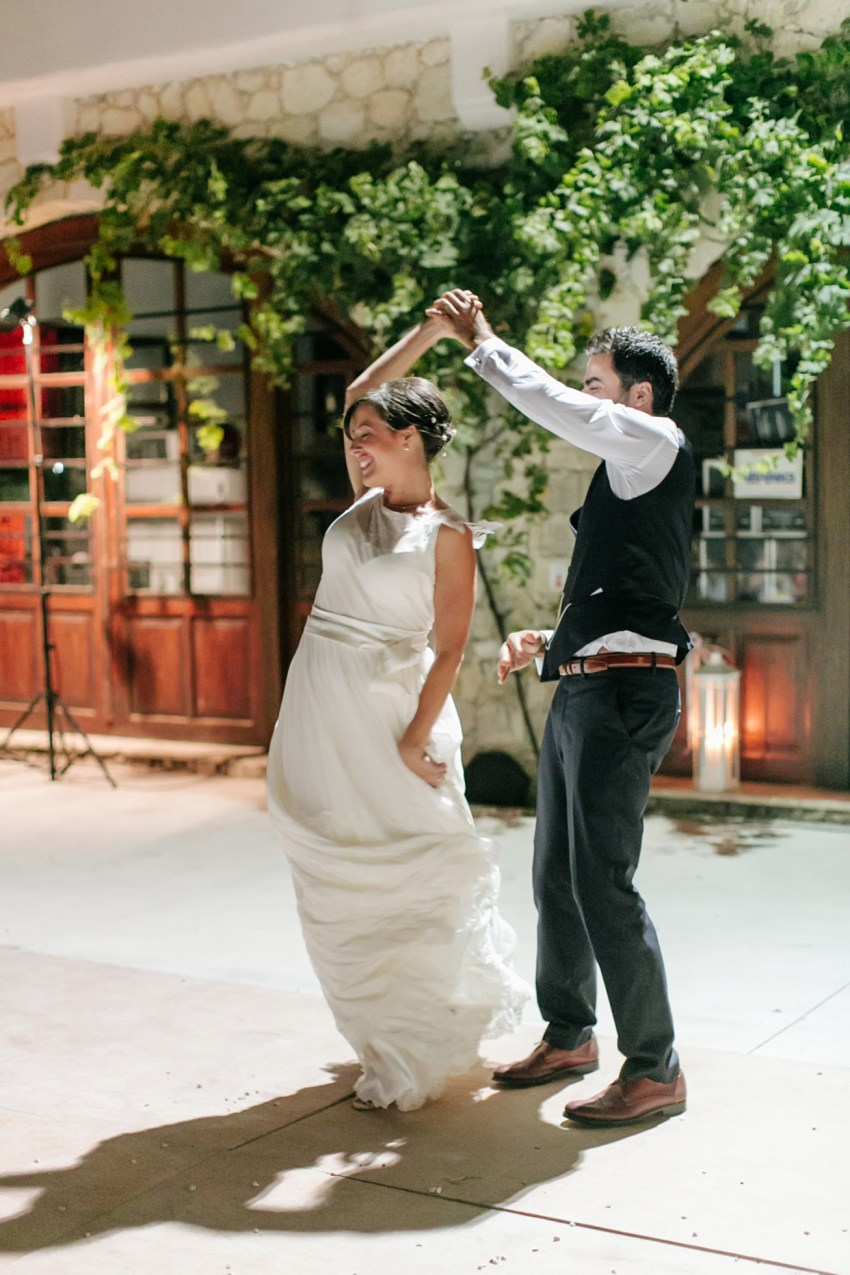Fine art portraits of a beautiful trendy couple on their wedding day reception, bride and groom are dancing and having fun in Dourakis winery in Chania Crete.