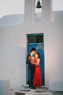 Beautiful Asian couple from Hong Kong is posing for the wedding photographer for their sunset engagement portraits in Imerovigli village Santorini. They're smiling and having good time, wearing formal designer outfits.