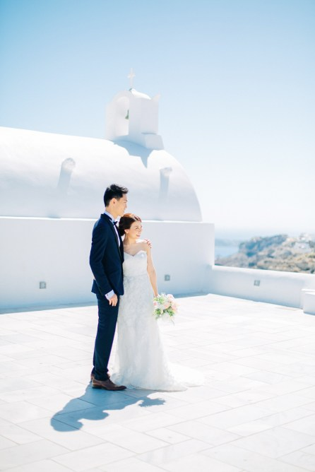 Professional Santorini wedding day photoshoot, groom and bride are posing with the picturesque background of Oia, seaview and clear blue skies.