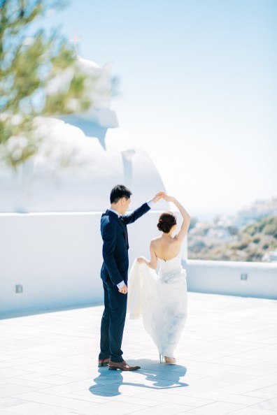 Professional Santorini wedding day photoshoot, groom and bride are dancing with the picturesque background of Oia, seaview and clear blue skies.