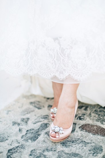 Professional Santorini wedding day photoshoot, close up photograph of bride's wedding dress and shoes while she's walking the pebbled streets of Oia. Light pink bridal shoes made by MiuMiu shoe brand.