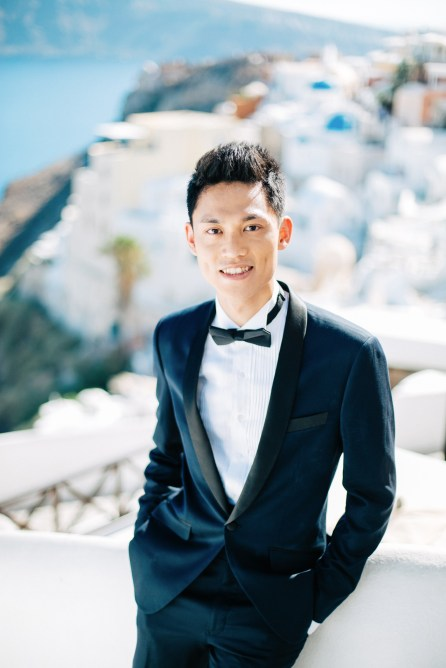 Professional Santorini wedding day photoshoot, groom is posing for his formal portraits wearing a tuxido and a bow tie with Oia caldera view, sea view and sunny blue skies in the backdrop.