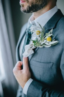 Close up image of an elegant groom's boutonniere. He's posing for portraits on his wedding day in Chania, Crete.
