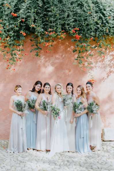 Beautiful bride with group of her bridesmaids posing for the wedding photographer on a summer wedding in Chania, Crete.