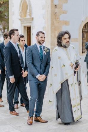 Stylish groom awaiting his bride prior to the wedding ceremony in Profitis Ilias, Chania, Crete.