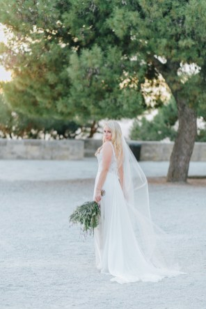 Elegant classy bride posing for wedding day bridal portraits holding flowers in Chania, Crete.